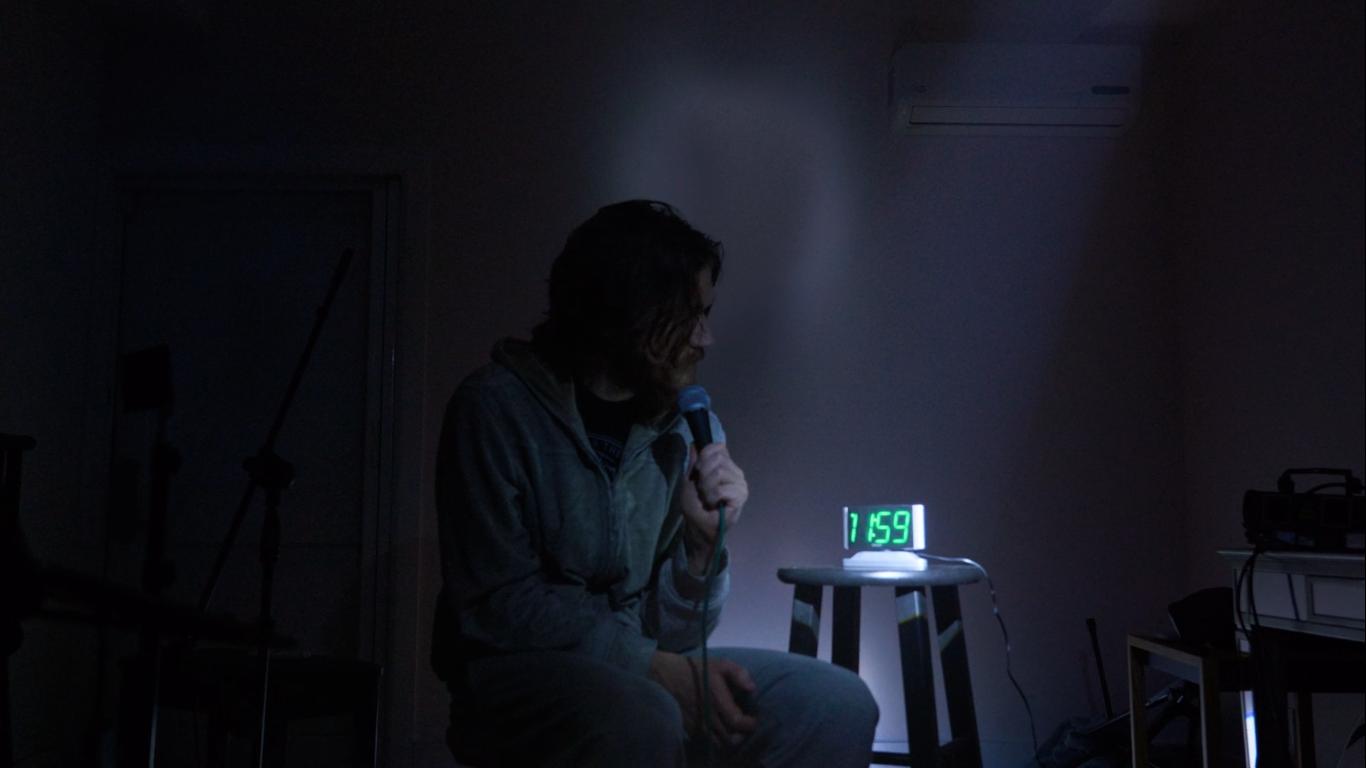 Cena de Inside. Bo Burnham está sentado num banco vestindo calça e jaqueta moletom cinza. Ele segura na mão um microfone à altura da boca. Ao lado dele um relógio digital, que projeta o horário numa luz verde, indica que são onze e cinquenta e nove. A sala é Mal iluminada e tem uma iluminação azulada.