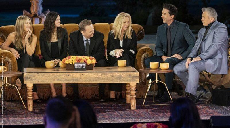 Cena de Friends: The Reunion. Da esquerda para a direita, sentado num sofá laranja está Jennifer Aniston, Courteney Cox, Matthew Perry e Lisa Kudrow. À direta, sentado em bancos de madeira estão David Schwimmer e Matt LeBlanc. Na frente do sofá laranja há uma mesa de madeira. Nela há três xícaras de café amarelas. Ao centro da mesa há um arranjo de flores e uma placa preta escrito RESERVED em branco. À direita há uma mesinha redonda de madeira. Nela há duas xícaras amarelas de café. Eles estão em um ambiente noturno a céu aberto. O chão é coberto por um tapete em tons escuros de vermelho e azul.