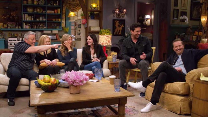 Cena de Friends The Reunion. À esquerda está Matt LeBlanc, ele está de braço esticado, apontado para Matthew Perry. À direita de Matt está Lisa Kudrow, ela está segurando uma almofada laranja. À direita está Jennifer Aniston, ela está de pernas cruzadas e com a mão na altura do rosto. À direita dela está Courteney Cox, ela está de pernas cruzadas e olhando para Jennifer. Os quatros estão sentados num sofá branco. À direita do sofá, David Schiwmmer está sentado numa cadeira amarela. Ele está olhando para Matthew Perry que está do seu lado, sentado numa poltrona amarela. Ele também está de pernas cruzadas. Ao centro há uma mesa baixa de madeira. Nela temos um arranjo de flores rosas, uma cesta de frutas e alguns copos de vidro azuis de água. O fundo é o cenário da cozinha de Monica Geller.