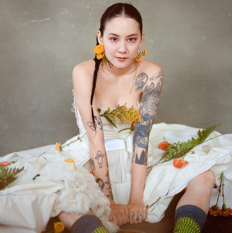 Texto alternativo: Fotografia de Michelle Zauner. A artista está sentada e veste um grande vestido branco sem alças, cabelo em trança e grandes brincos florais. Há folha e flores espalhadas sobre ela. O fundo é cinza.