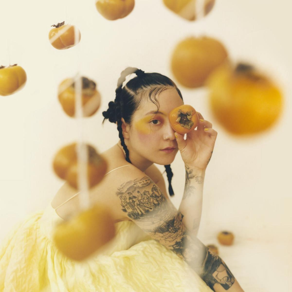 Capa do disco Jubilee, de Japanese Breakfast. A cantora Michelle Zauner na está na capa do disco, vestindo um vestido amarelo, maquiagem artística no mesmo tom e tranças no cabelo. Há caquis pendurados no primeiro plano e ela segura um na frente do olho direito.O fundo é claro, quase branco. Há também muitas tatuagens em seu braços.