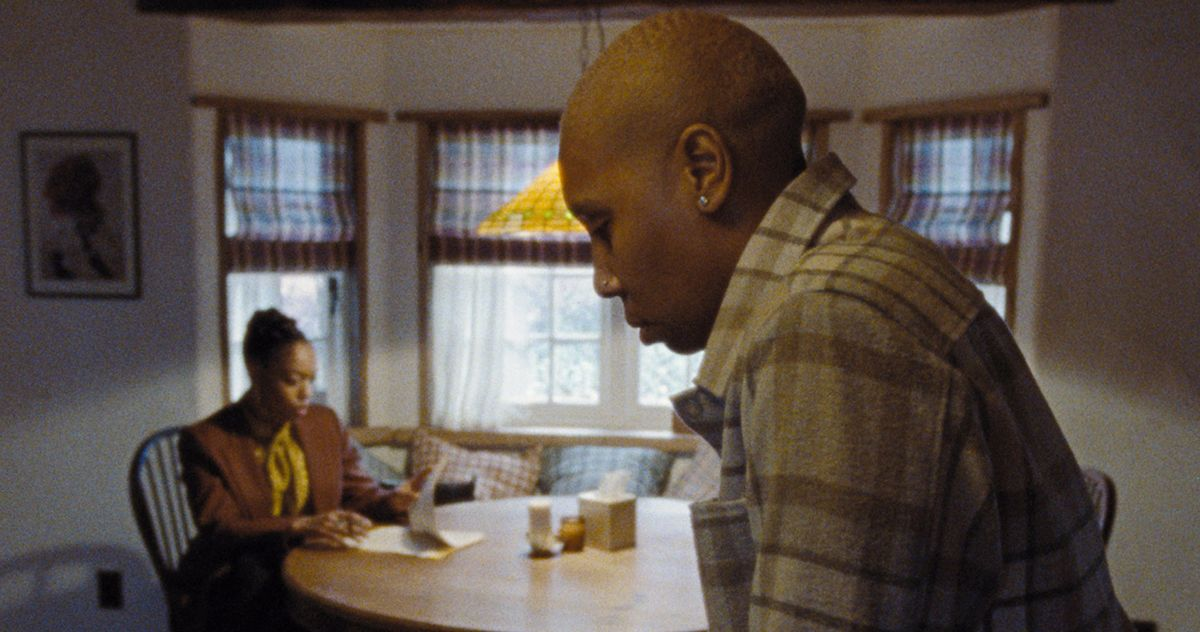 Cena da série Master of None Presents: Moments in Love. Nela, vemos Denise e Alicia, duas mulheres negras. Denise está de perfil, focada, é careca e olha para baixo, triste. Alicia está sentada à mesa, ao fundo e desfocada.