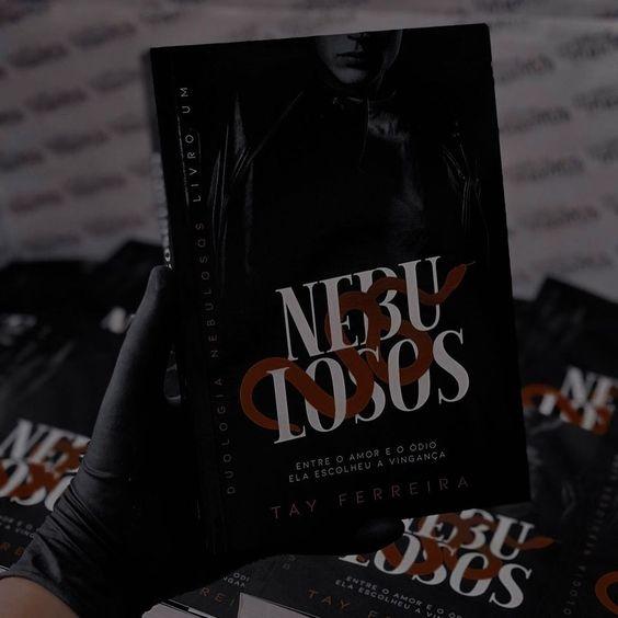 """Em uma mão usando luva preta está o livro Nebulosos. A capa é preta, com a imagem de um homem vestindo jaqueta de couro no fundo. Na frente dele está escrito """"NEBULOSOS"""" em branco, com o desenho de uma cobra vermelha passando entre as letras. Em baixo está a frase """"ENTRE O AMOR E O ODÍO ELA ESCOLHEU A VINGANÇA"""" de branco e """"TAY FERREIRA"""" de vermelho. No fundo, há outras copias do livro."""