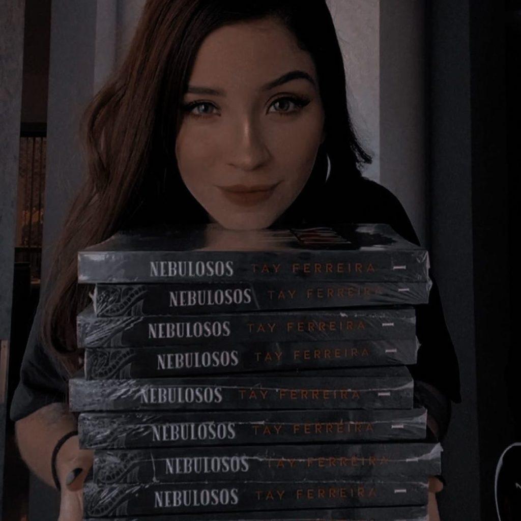 Foto de Tay Ferreira. A mulher tem cabelo castanho escuro e longo, olhos claros e pele branca. Ela veste uma blusa preta, e olha para câmera com um sorriso. Em suas mãos estão várias copias do seu livro, nebulosos.