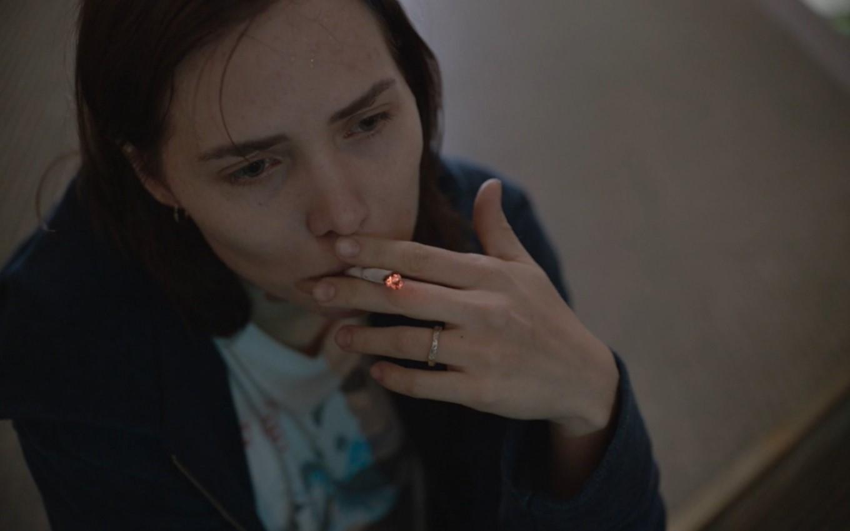 A imagem é uma foto da série Onde Está Meu Coração. Nela, a personagem Amanda, interpretada por Letícia Colin, está sentada fumando um cigarro, segurando com a mão esquerda. Ela veste uma camisa branca com desenhos e um moletom escuro. Amanda é uma mulher branca, de cabelos castanhos escuros na altura dos ombros, ela usa uma aliança no dedo anelar da mão esquerda.
