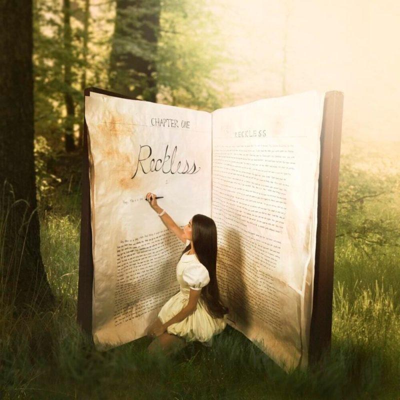 """Foto promocional de Reckless. Madison, mulher branca e magra, de cabelo castanho longo, usa um vestido branco curto e bufante. Ela está ajoelhada, escrevendo em um livro grande que está aberto ao seu redor. Dentro da página está escrito """"chapter one"""" e """"Reckless"""", seguidas por um texto ilegível. Do lado esquerdo da imagem há algumas árvores, e do lado direito vem uma luz branca. O chão é todo gramado."""