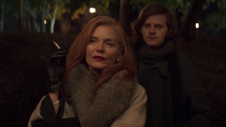 Cena do filme French Exit. A imagem mostra, em primeiro plano, a personagem Frances, interpretada por Michelle Pfeiffer, uma mulher branca de cabelos lisos e ruivos. Ela está num parque, de noite, e segura um cigarro com a mão direita, coberta por uma luva preta, e usa um sobretudo bege com uma gola de pelos cinzas. Frances também usa um batom vermelho cereja e olha para fora da imagem com os olhos semicerrados. Atrás dela, em segundo plano e levemente desfocado, está Malcolm, personagem de Lucas Hedges, um homem jovem branco de cabelos lisos loiros. Malcolm olha para o mesmo lugar que Frances com um expressão neutra. Ele veste uma blusa cinza escura e um cachecol preto.