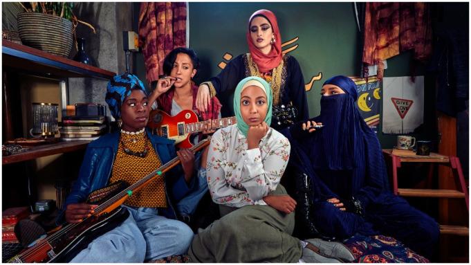 Foto promocional da primeira temporada de We Are Lady Parts. Cinco mulheres de frente para a câmera, em um cenário caseiro. No centro, Amina (Anjana Vasan), sendo observada pelas outras quatro, sentada de pernas dobradas, olhando para a câmera e usando uma saia cinzenta e uma camisa branca de estampa floral rosa, com a mão esquerda segurando o queixo e um hijab verde claro cobrindo a cabeça. Também sentada, à sua direita está Momtaz (Lucie Shorthouse), usando um niqab azul escuro que cobre inteiramente seu corpo, deixando apenas os olhos à vista. Ela também usa luvas pretas e pulseiras punks, segurando um cigarro eletrônico. Atrás delas e de pé, Ayesha (Juliette Motamed), usando uma túnica leve azul com detalhes dourados e uma camiseta com estampa por baixo e um hijab de cor pêssego, com a mão esquerda apoiada no ombro de Saira (Sarah Kameela Impey). Ela está sentada atrás de Amina, com uma palheta entre os dentes, segurando uma guitarra no colo. Ela usa uma camisa sem mangas xadrez vermelha e preta com uma camiseta cinza por baixo, os cabelos pretos e curtos soltos atrás. Na frente dela, Bisma (Faith Omole), também segurando uma guitarra no colo e usando calças jeans largas, uma camiseta amarela com padrões pretos por baixo de uma jaqueta de couro azul escura e colares de contas, com um turbante azul claro com listras escuras.
