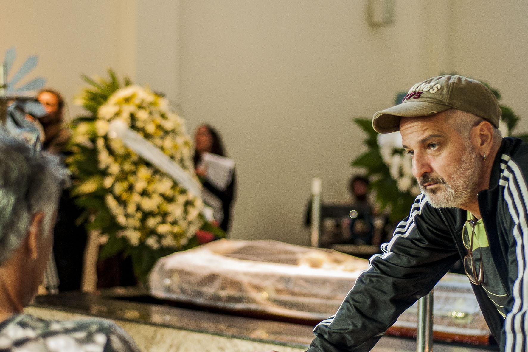 Foto de Lírio Ferreira. O diretor está no canto direito da imagem, projetado parcialmente na foto. O foco está nele, desfocando todo o resto. De fundo, é possível ver o cenário de um enterro, com um caixão e muitas flores.