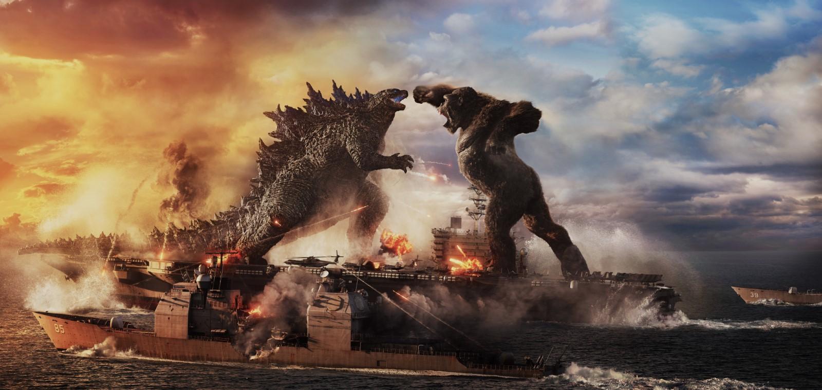 Cena do filme Godzilla vs. Kong. A imagem é retangular e a região central é dividida entre duas figuras que estão frente a frente. Na região central esquerda, tem o Godzilla, um lagarto gigante e bípede, sua boca está aberta e de dentro dela sai um brilho azul. Nas suas costas há protuberâncias em formato triangular e espinhoso, elas se estendem da base da sua nuca até a ponta da sua cauda. Na região central direita, tem o Kong, um gorila gigante e bípede, sua pelagem é preta e cobre todo o corpo, com exceção das mãos, barriga, tórax, pés e rosto. Sua boca está aberta na intenção de dar um grito. Seu punho direito também está levantado e está pronto para desferir um soco no rosto de Godzilla. Ambas as figuras estão em cima de um grande navio porta aviões, que está no mar. No canto inferior da imagem pode-se observar o mar e há navios na região central, o qual possui canhões e está disparando contra o Godzilla. O fundo é dividido também, na parte esquerda o fundo é o céu alaranjado e com bastante fumaça, na parte direita, o fundo é o céu azul e com nuvens.