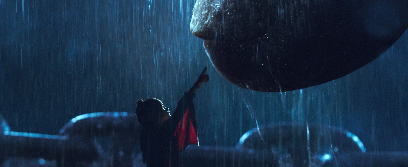 Cena do filme Godzilla vs Kong. A imagem é retangular. na região central há uma garota de aproximadamente 11 anos, ela tem um tom de pele amendoado, seus olhos são castanho claro, o cabelo é castanho escuro e está preso em um coque no topo da cabeça. Ela está de perfil, mostrando apenas o lado direito do rosto. Suas vestes são vermelhas e bem largas, sobrando tecido em algumas partes. Seu braço está levantado. Ela aponta para o canto superior direito, em direção a ponta do dedo indicador do Kong, que aparece apenas um pedaço do dedo e da sua unha. A cena se passa à noite e chove. O fundo da imagem é azul e na parte inferior podemos observar as grandes correntes que prendem o Kong.