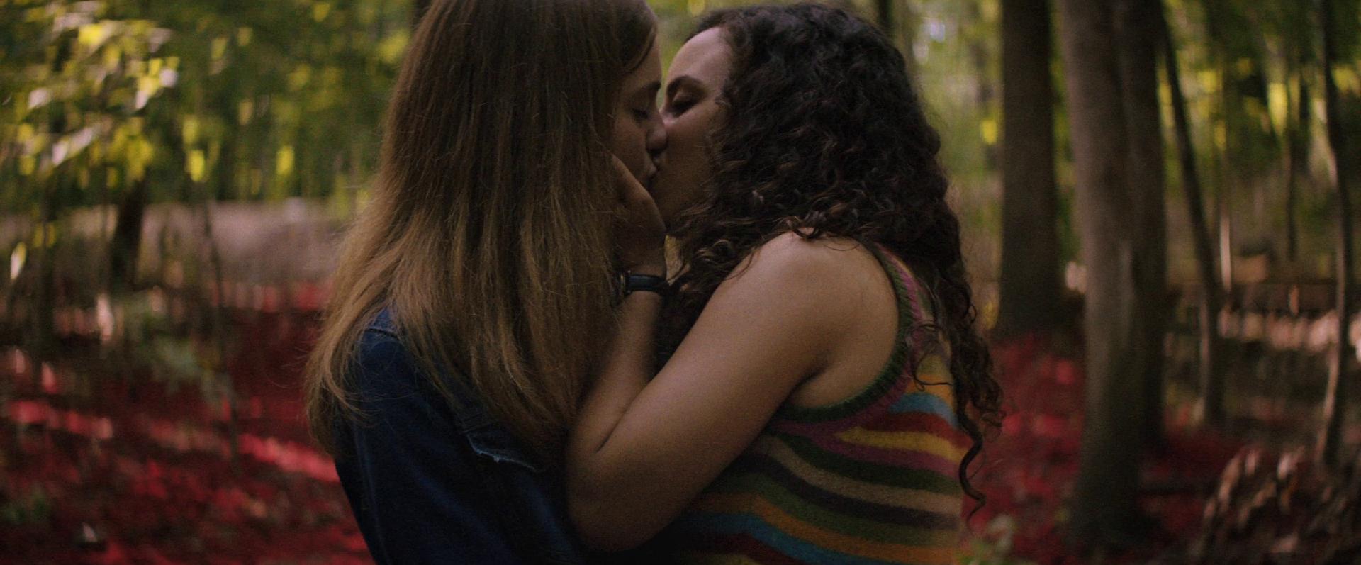 Cena do filme Rua do Medo: 1666 - Parte 3. Na cena, vemos Deena e Sam se beijando. À direita, Deena é negra de pele clara, tem cabelos cacheados e usa uma regata amarela com detalhes listrado em azul, vermelho e amarelo. À esquerda, está Sam, branca e loira, usando jaqueta jeans. Elas estão em uma floresta com flores vermelhas ao redor.