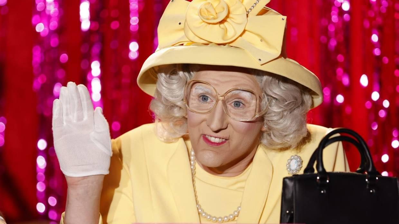 Foto da drag queen Anita Wig'lit caracterizada como a Rainha Elizabeth, de terninho amarelo e luvas brancas, acenando gentilmente no painel do Snatch Game de Drag Race Down Under.