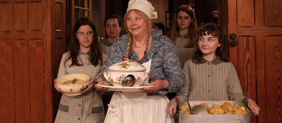Cena do filme A Boa Esposa. Uma mulher mais velha está no centro da imagem, com roupas de cozinheira segurando um prato de porcelana. Ao seu redor, garotas jovens uniformizadas a olham com orgulho.