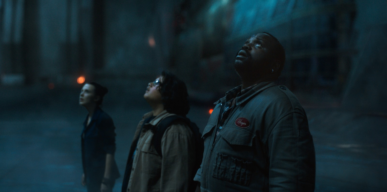 Cena do filme Godzilla vs. Kong. É uma imagem retangular, na qual há três pessoas enfileiradas, lado a lado, em uma ordem decrescente de altura da direita para a esquerda, de modo que a pessoa da extrema direita está mais à frente da imagem, e a pessoa da extrema esquerda está mais ao fundo da imagem Todos aparecem da cintura para cima. O personagem da direita é Bernie, um homem negro, seus olhos são castanhos escuros, seu nariz é largo e seus lábios são grossos. Ele possui uma barba rala e seu cabelo é curto, sendo quase rente a cabeça. Ele usa um macacão verde com bolsos na altura do peitoral e da barriga. Na parte central da imagem aparece Josh, um adolecente de pele com tom amendoado, seus olhos, de cor castanho claro, seu cabelo é preto e grande, ele usa um óculos retangular. O personagem usa uma jaqueta bege e carrega uma mochila preta nas costas. Na parte esquerda da imagem aparece Madison, uma garota branca, com olhos castanhos claros. Seu cabelo é grande e castanho claro, na imagem ele aparece preso em um coque. Ela usa uma jaqueta azul, com as mangas dobradas na altura do cotovelo, e em seu braço esquerdo há um conjunto de pulseiras. Todos os personagens olham para o canto superior esquerdo da imagem, Bernie e Josh estão com as bocas abertas. O fundo da imagem é de tom azul escuro.