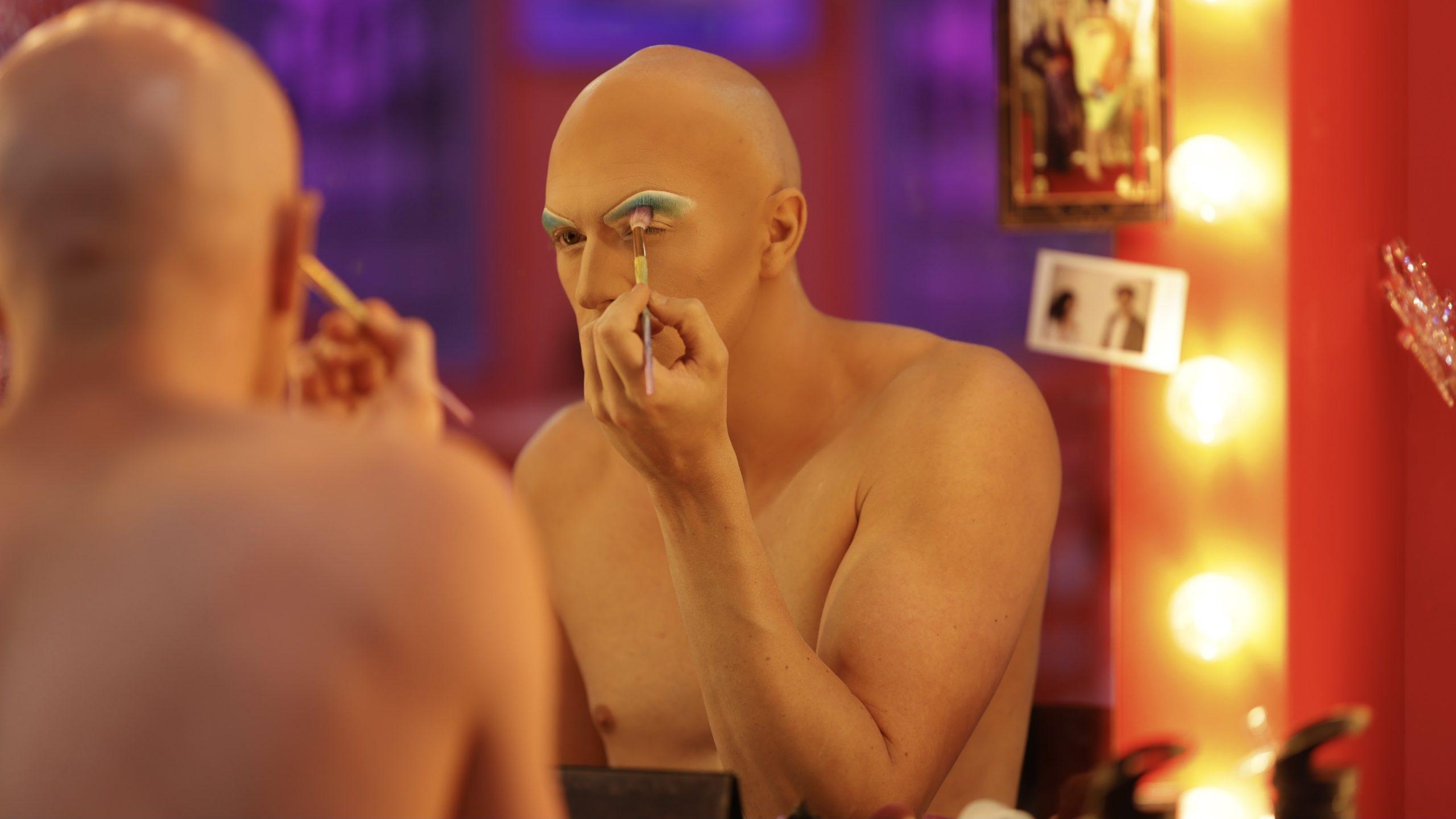 Cena de Drag Race Down Under, com a drag queen Elektra Schock desmontada, e se maquiando. Ela é careca, branca e está sem camisa, desenhando uma sobrancelha azul acima do olho.