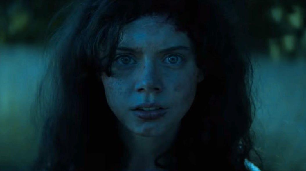 Cena do filme Rua do Medo: 1666 - Parte 3. Na cena, vemos a Sarah Fier original em close, uma mulher branca, de olhos azuis e cabelo preto. Ela tem uma expressão de medo no rosto, e a foto foi tirada de noite.