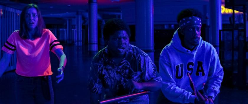 Cena do filme Rua do Medo: 1666 - Parte 3. Na cena, vemos três personagens de noite no shopping, com as luzes apagadas e um contraste neon muito forte.