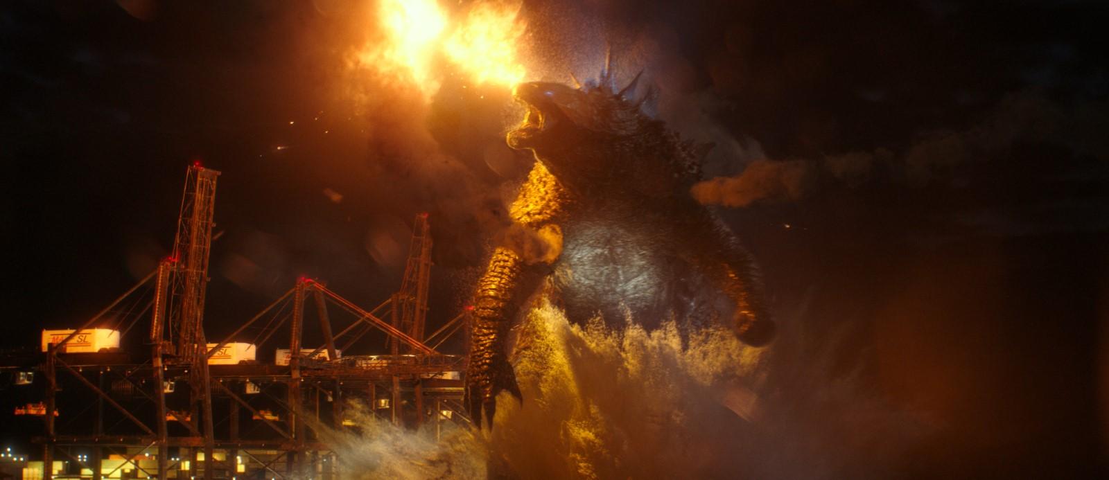 Cena do filme Godzilla vs Kong. A imagem é retangular e no centro dela está o Godzilla, um lagarto gigante e bípede, ele é mostrado da cintura para cima e olha para frente. Na imagem ele está saindo da água, seus olhos e suas protuberâncias na costas brilham em azul. Atrás dele há algumas construções e vigas vermelhas. Acima de sua cabeça ocorre uma explosão. O fundo da imagem é o céu noturno.