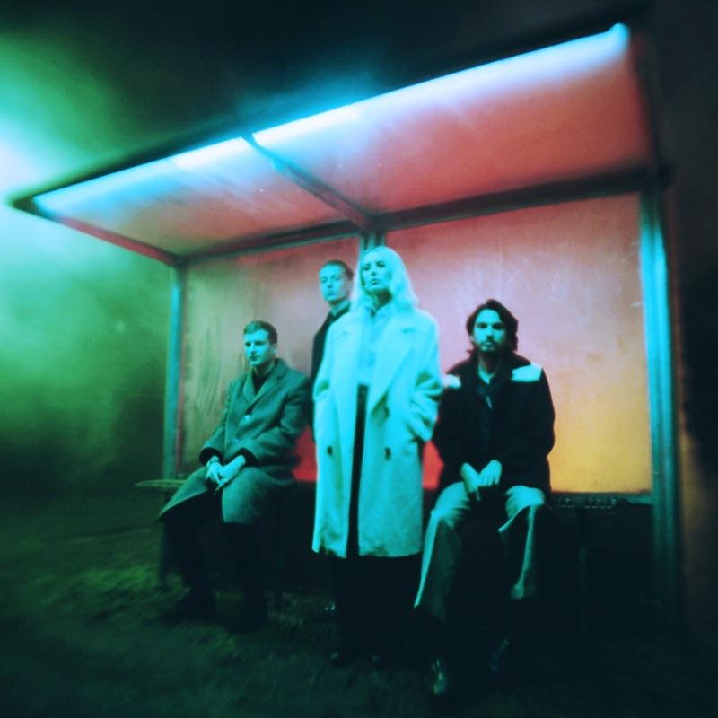 Capa do álbum Blue Weekend, da banda Wolf Alice. Os quatro membros estão sentados em um ponto de ônibus e está de noite. Eles usam casacos longos. A vocalista, uma mulher branca de cabelos brancos, está de pé. As cores utilizadas na iluminação criam um efeito nostálgico, a partir dos tons de vermelho, verde e azul utilizados.