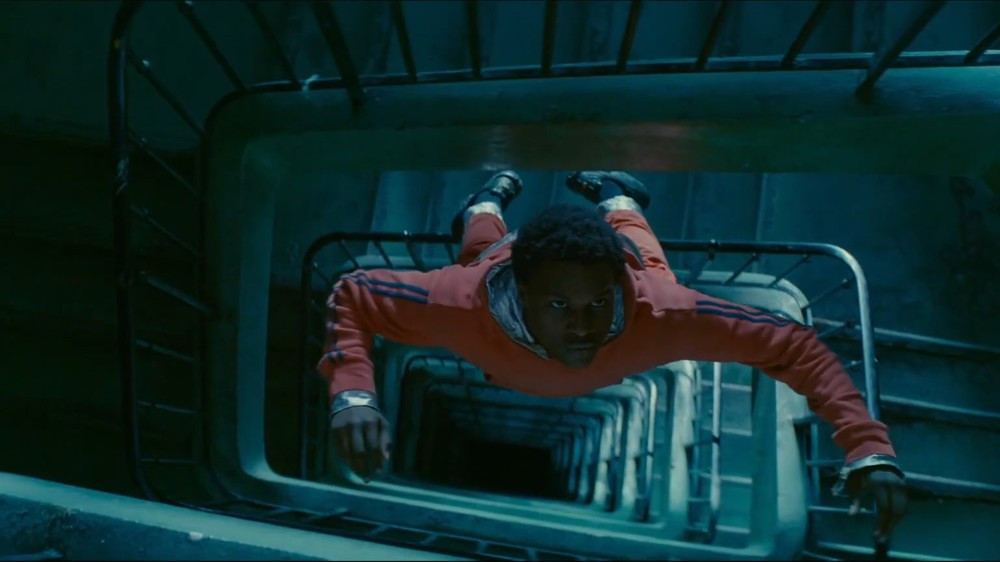 Cena do filme Edifício Gagarine. Ao centro da foto está Youri, um jovem negro vestindo um macacão de astronauta. Ele é visto de cima, flutuando ao centro de uma escada quadrada em caracol. Ele olha para cima.