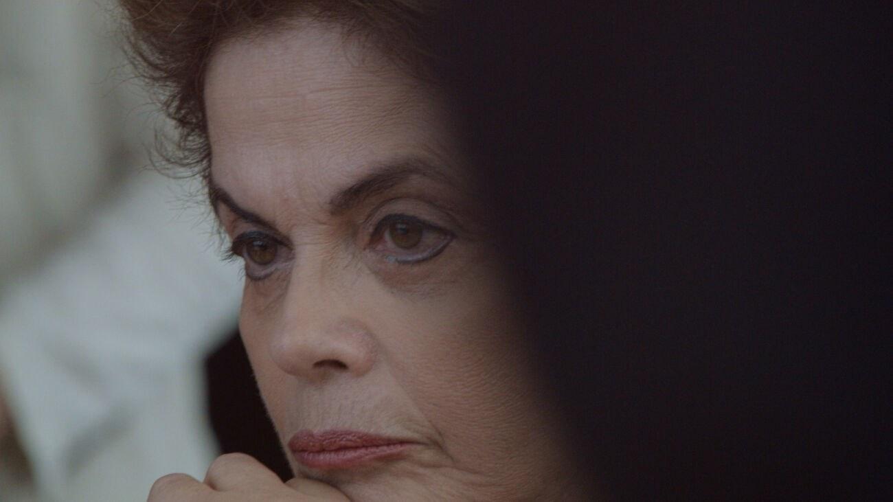 Cena do filme Alvorada. A imagem é retangular e mostra o lado esquerdo do rosto de Dilma Rousseff. Ela é uma mulher branca, de olhos castanhos e cabelos também castanhos curtos. Dilma usa maquiagem preta no contorno dos olhos e um batom rosa cor de boca. Dilma está olhando para fora da imagem, para o lado esquerdo, com o rosto inclinado. Na diagonal direita, da metade da foto em diante, existe uma sombra escura.