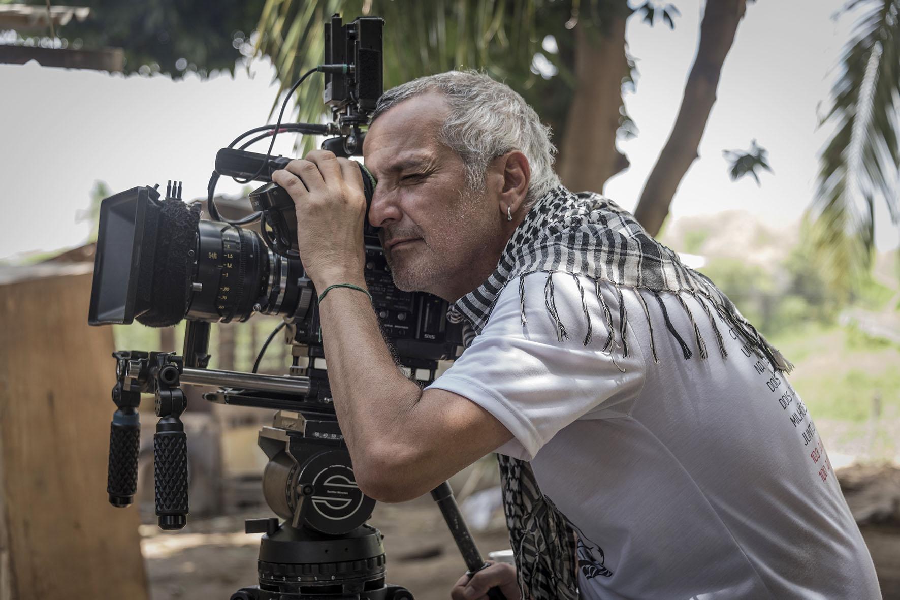 Foto do diretor Lírio Ferreira. Ele está de perfil, olhando pela lente de uma câmera de filmagem em um tripé. Lírio é um homem branco de 50 anos, com cabelos grisalhos e ralos. Ele usa uma camiseta branca e um chale por cima.