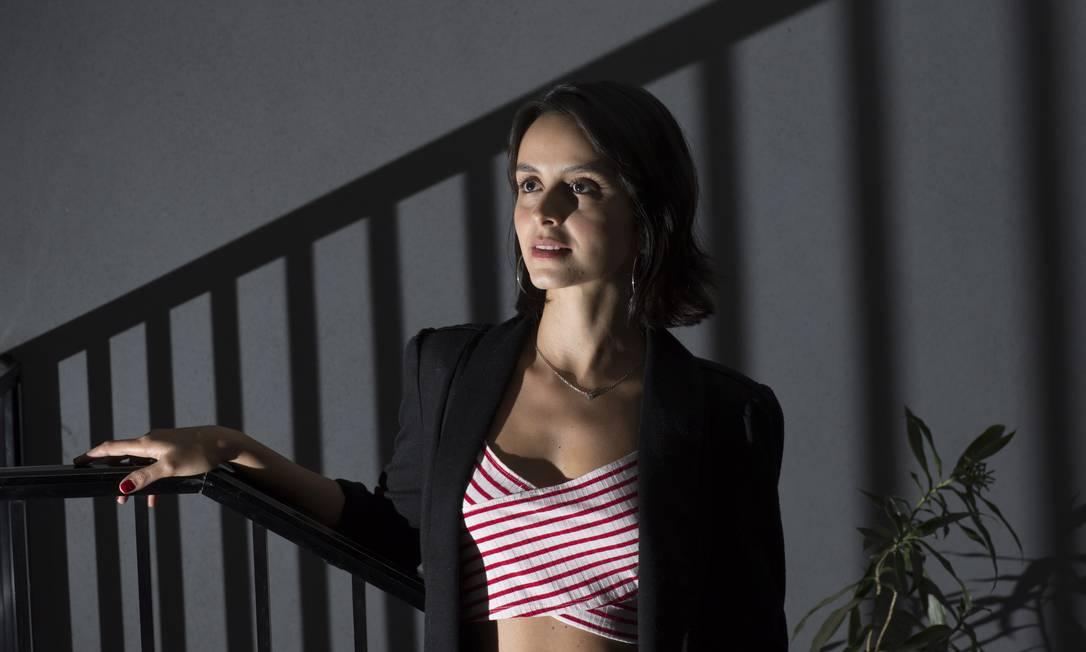Foto de Alinei Bei, uma mulher branca de 30 anos com cabelos pretos na altura dos ombros. Ela usa um blazer preto e um cropped com listras brancas e vermelhas. Podemos vê-la da cintura para cima, com a mão direita em um corrimão. As sombras do corrimão estão projetadas em toda a imagem.