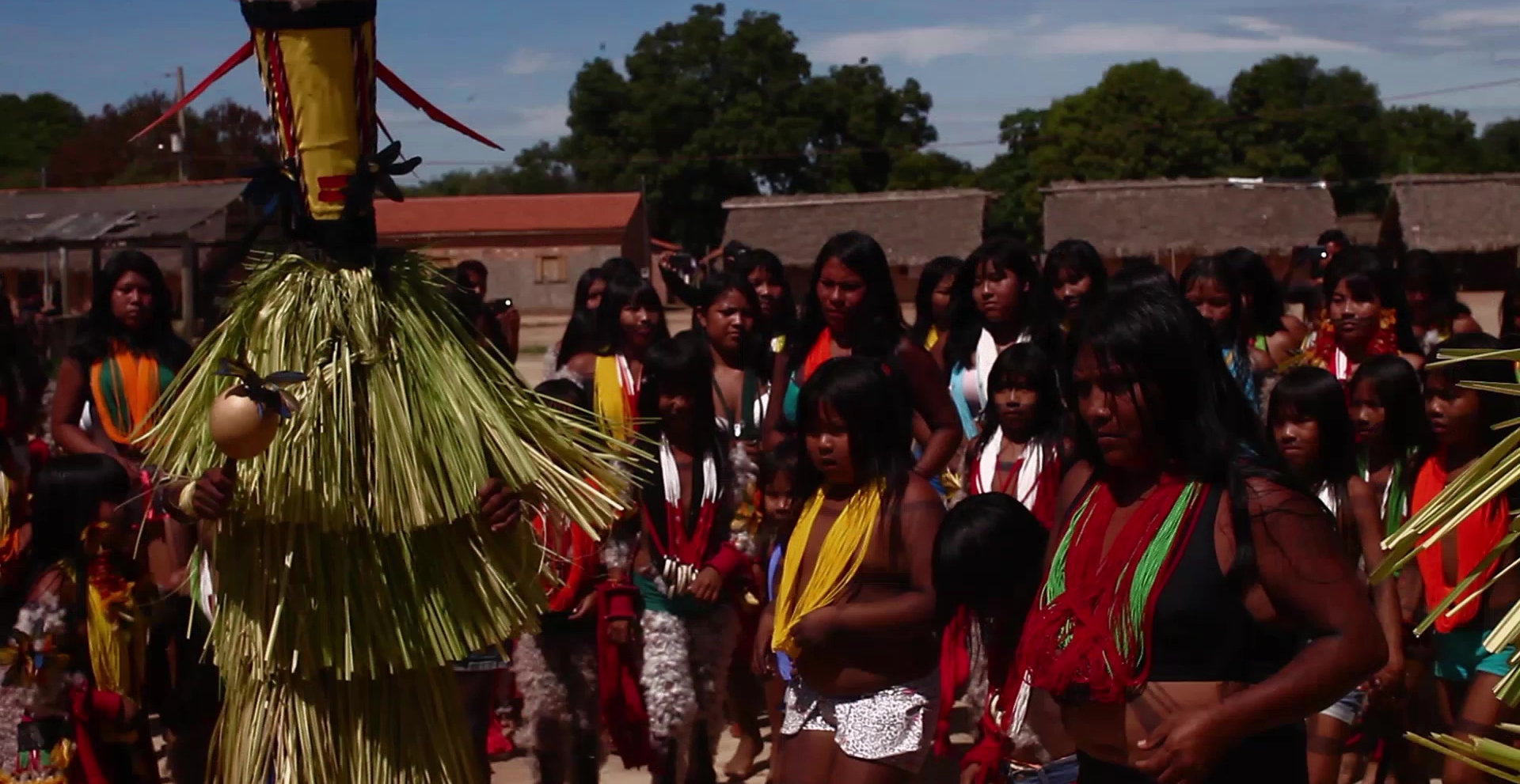 Cena do filme Apyãwa (Tapirapé) Iraxao Rarywa que exibe diversos indígenas, em sua maioria mulheres, vestindo roupas típicas de sua cultura, em volta de uma pessoa que usa uma vestimenta desfiada e toca um chocalho. O fundo é composto por casas, árvores e o céu azul.