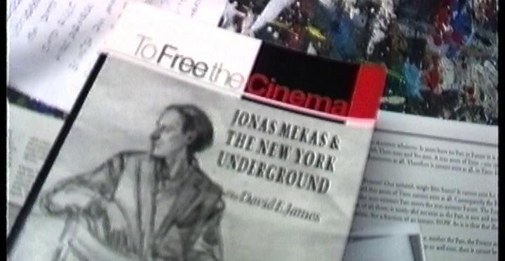 Cena do filme Com Amor: Volume 1 1987-1996 exibe livros espalhados, sendo que um deles se chama Para Libertar o Cinema, em inglês, e apresenta o desenho de um homem sentado em uma cadeira olhando para trás.