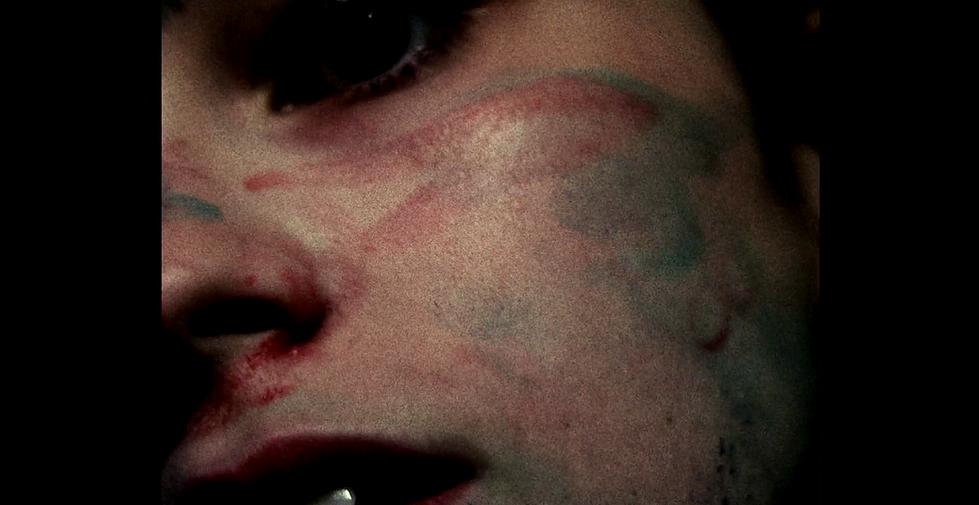 Cena de Chorar exibe metade do rosto de uma mulher, inclinado e pintado por tinta vermelha e verde, já seca.