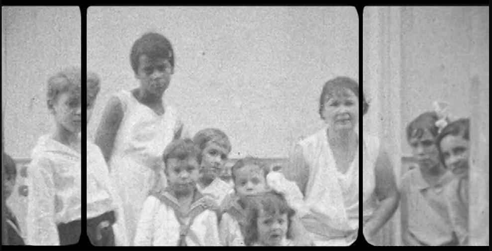 Cena do curta Descompostura exibe uma foto em preto e branco em que uma mulher negra olha descontente para a câmera, enquanto está rodeada de pessoas brancas.