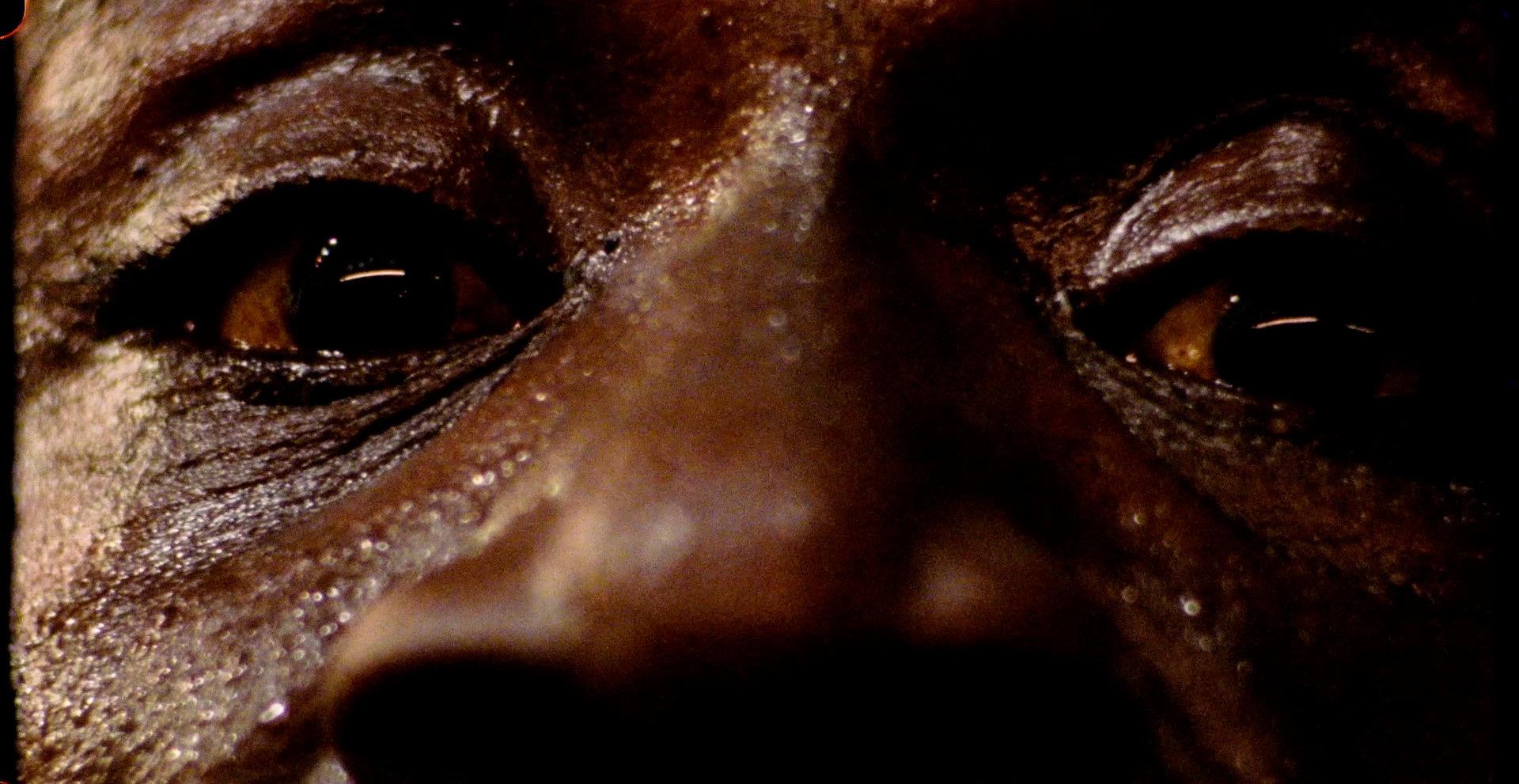 Cena do filme Eu Ando Sobre a Água em que aparece um homem negro bem de perto, sendo visível apenas seus olhos e o nariz. Sua expressão é de tristeza.