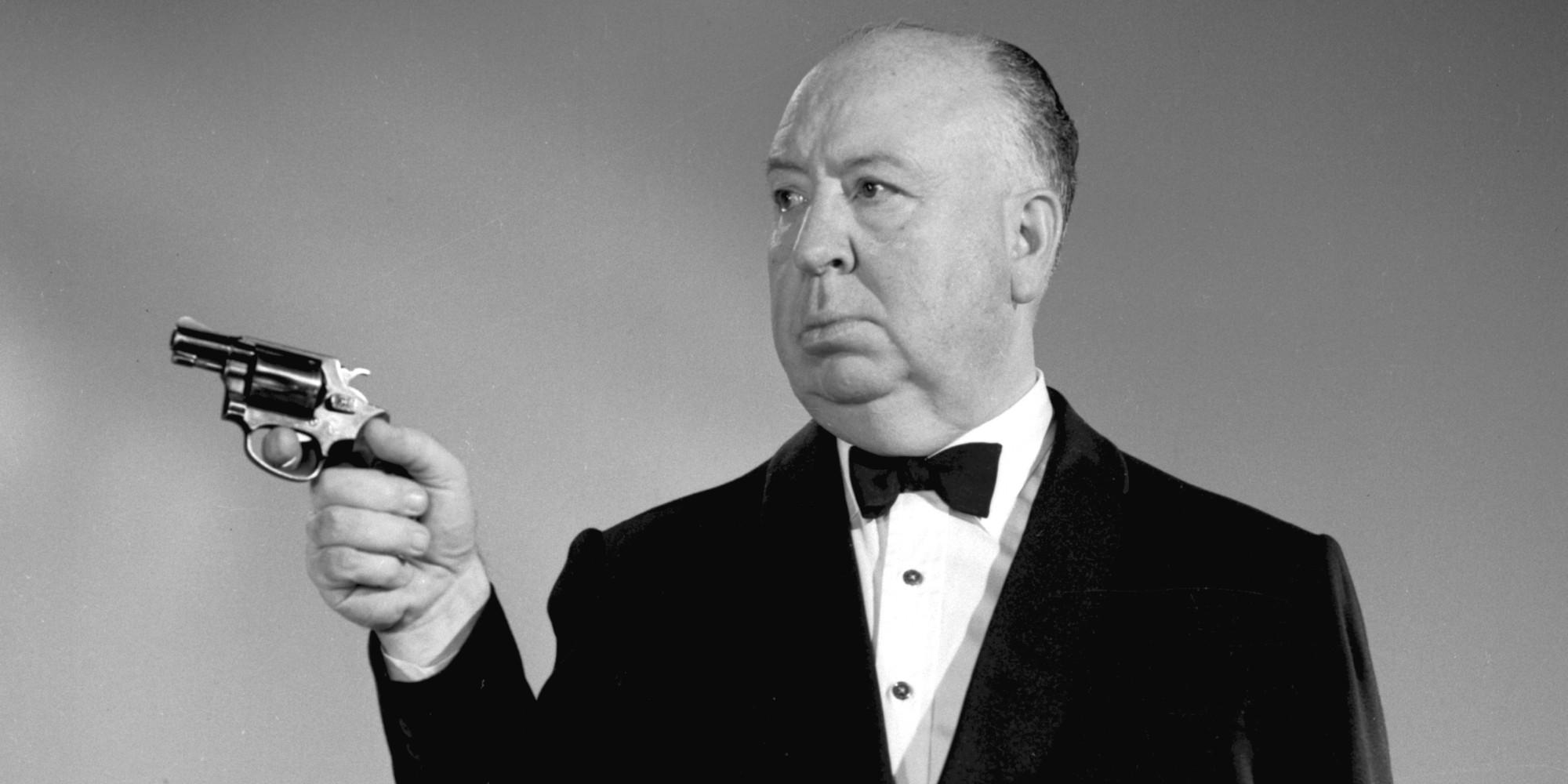 Vemos uma foto em preto e branco do Diretor Alfred Hitchcock, falecido em 1980. Ele é um homem branco, calvo e robusto que usa um smoking preto e aponta uma pistola para a nossa esquerda