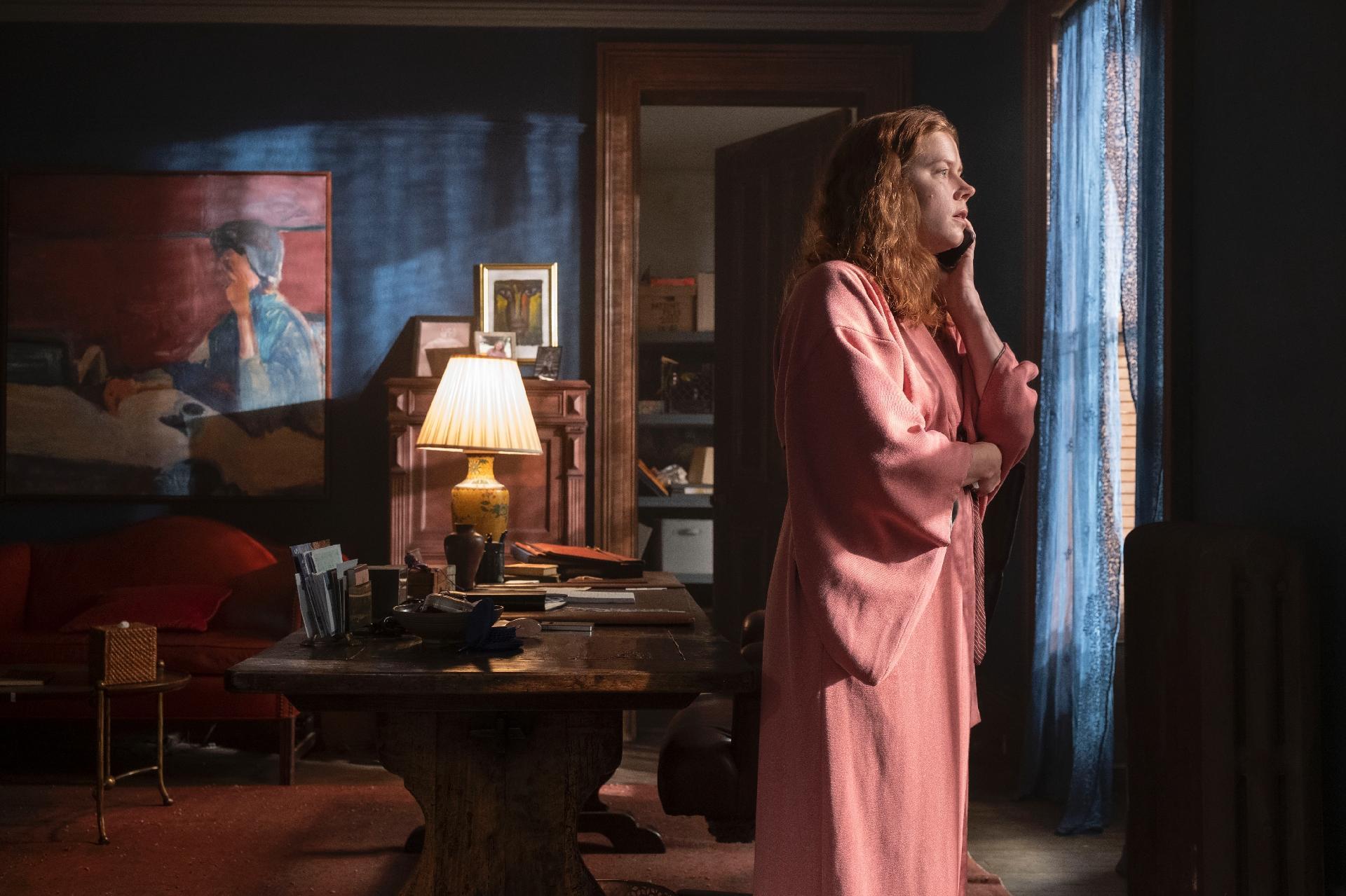 Vemos a personagem Anna Fox (Amy Adams) de frente para a janela de seu escritório, à direita. Ela é uma mulher branca, ruiva e usa um roupão rosa. A janela tem cortinas azuis e, ao fundo, vemos uma escrivaninha com diversos objetos em cima, incluindo um abajur amarelo. Na parede, podemos ver um quadro de um homem sentado, voltado para a esquerda. Assim, como o roupão de Anna e as cortinas, vemos o contraste de tons de azul no quadro e na parede com o tapete.