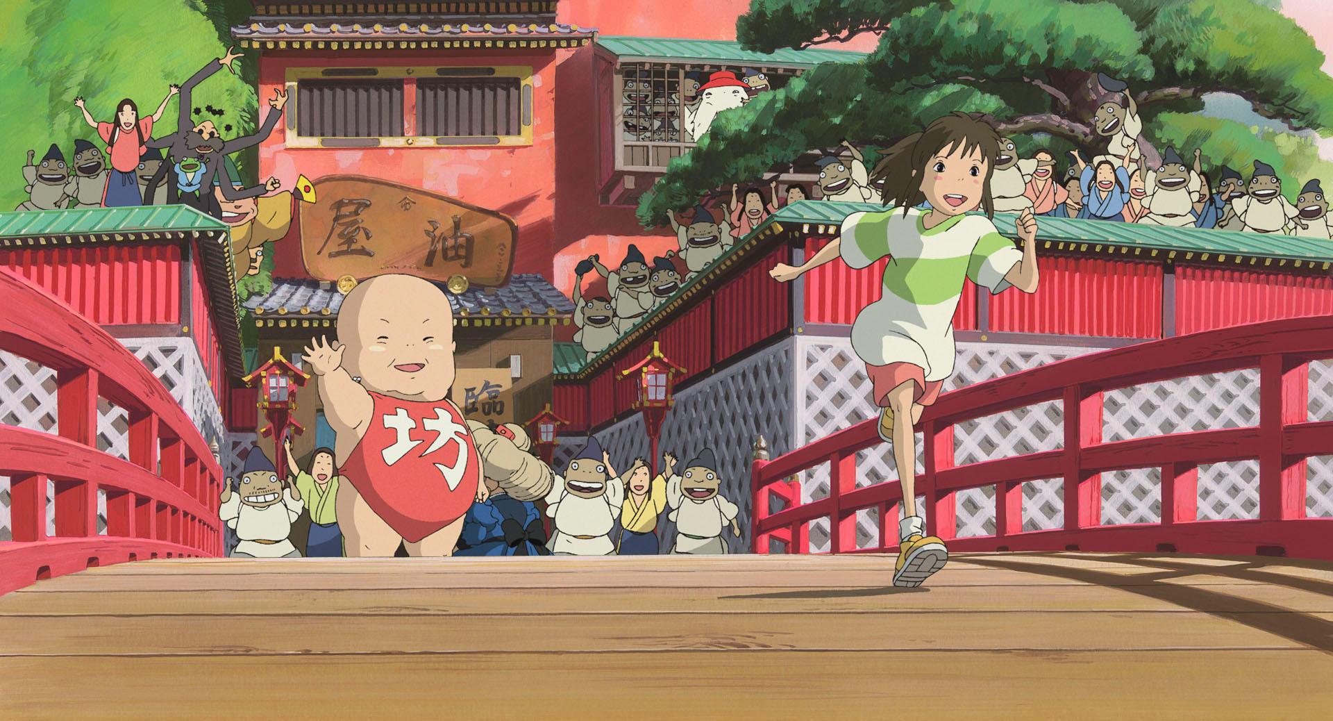"""Cena do filme de animação """"A Viagem de Chihiro"""". À frente, vemos Chihiro, uma garota asiática, pele branca, bochechas rosadas e cabelo castanho preso em um rabo de cavalo. Ela usa uma camisa branca e verde, um short vermelho e tênis amarelos. Ela está sorrindo eufórica, correndo em cima de uma ponte de madeira, enquanto uma multidão acalorada atrás dela se despede e comemora. Todos estão em um grande prédio de arquitetura japonesa, pintado de vermelho e branco, com os tetos esverdeados. A cena se passa de dia."""