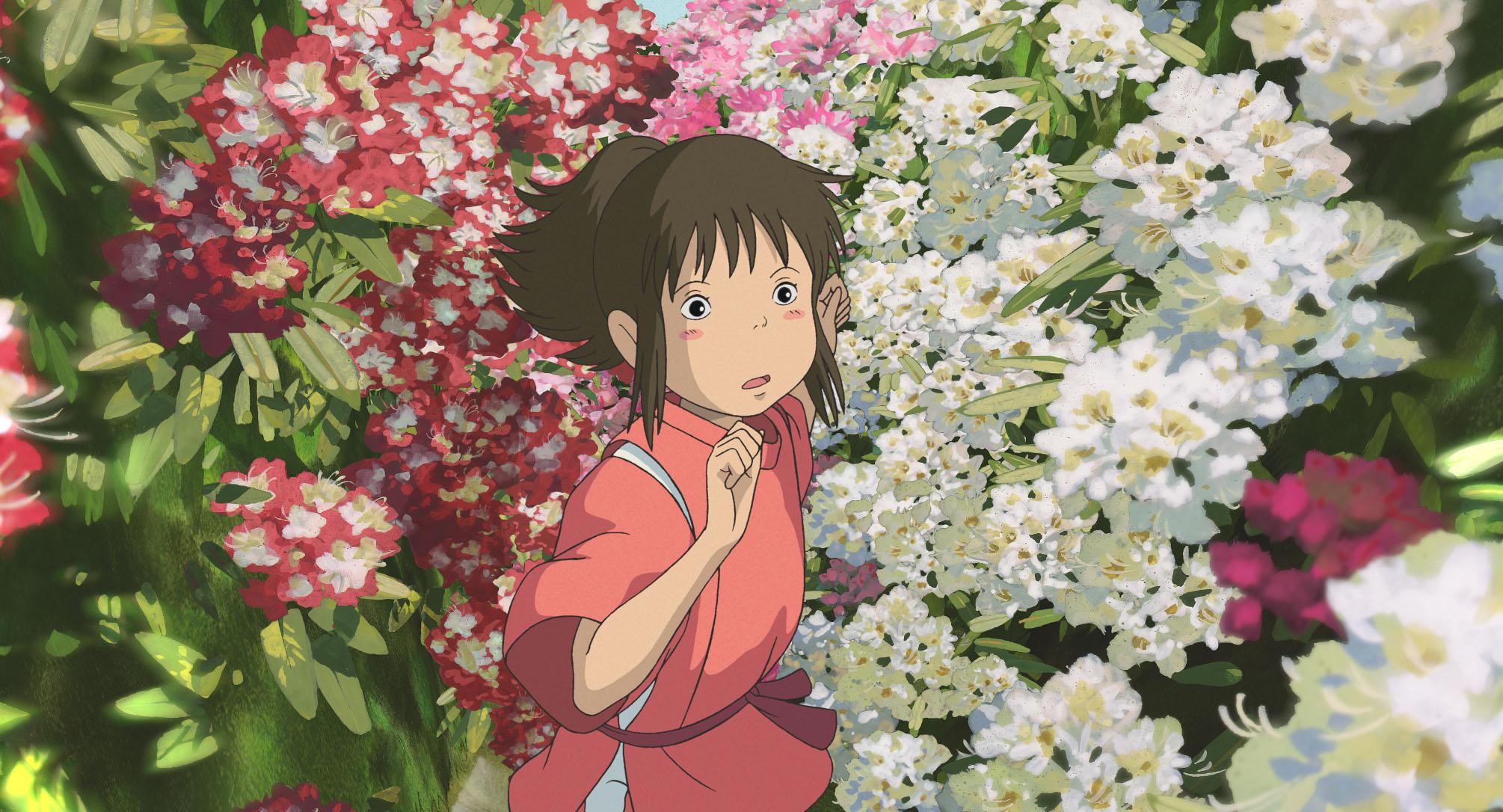 """Imagem do filme de animação """"A Viagem de Chihiro"""". A cena se passa de dia. No centro, vemos Chihiro, uma garota asiática, de pele branca, bochechas rosadas e cabelos castanhos presos em um rabo de cavalo, vestindo um kimono vermelho. Ela se esgueira entre um grande jardim de flores brancas e vermelhas, e seu semblante é confuso."""