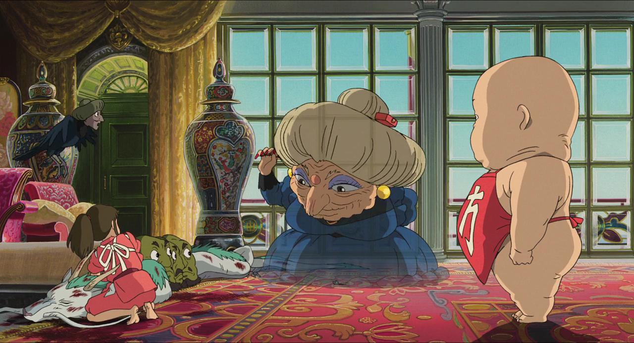 """Imagem do filme de animação """"A Viagem de Chihiro"""". A cena se passa dentro de um quarto luxuoso, com um longo tapete vermelho no chão, poltronas elegantes, um grande vaso de pintura estilizada e sofisticada e ao fundo duas grandes janelas fechadas, que revelam o céu azulado do lado de fora. Ao centro, está Zeniba, uma mulher idosa, de torso curto e cabeça desproporcionalmente grande. Seu rosto é completamente enrugado, ela usa uma sombra roxa em suas pálpebras e seu cabelo longo e branco preso em um coque. Ela é ligeiramente transparente, podendo ser visto parte do fundo através dela, usa brincos de pérola dourados nas orelhas e veste um vestido azul. Sua mão direita, marcada pelas longas unhas vermelhas, está erguida, e ela olha pro chão, em direção a Chihiro: uma garota de pele branca e cabelos castanhos presos em um rabo de cavalo. Ela veste um kimono vermelho e está de costas para a câmera, sem que possamos ver seu rosto. Ela está agachada em frente à Haku, um dragão asiático branco com uma crina esverdeada que se estende por todo o seu corpo. Ele está com os olhos fechados, inconsciente, sangrando e claramente machucado. Ao lado dele, estão três cabeças avulsas, de pele verde e uma longa barba preta. As três estão de perfil, com um olhar assustado; e acima dele vemos um pequeno pássaro peculiar: seu corpo é de um corvo, com uma penugem escura, e sua cabeça é a de uma mulher idosa, cujo cabelo escuro é preso em um coque. O pássaro também olha para Zeniba, espantado. Além deles, do outro lado de Zeniba, está Bah, um bebê gigante, de pele branca, usando um avental vermelho. Ele está de perfil, com a cabeça virada para Zeniba, sem que possamos enxergar seu rosto.]"""