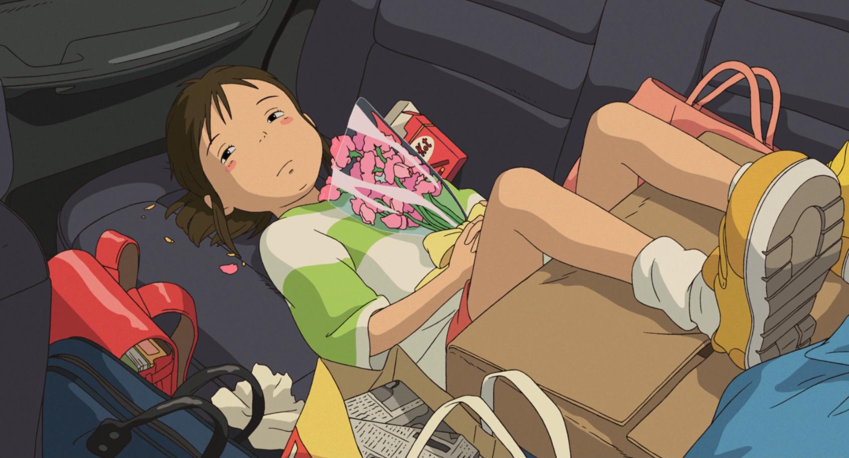 """Imagem do filme de animação """"A Viagem de Chihiro"""". A cena se passa de dia. Ocupando quase toda a imagem, está Chihiro, uma garota asiática, de pele branca, bochechas rosadas e cabelos castanhos presos em um rabo de cavalo. Ela veste uma camisa branca e verde, um short vermelho e tênis amarelos. Ela está deitada no banco de trás de um carro, que está abarrotado de malas e sacolas, com os pés apoiados em uma grande caixa de papelão. A menina olha para o lado, triste e melancólica, enquanto segura com as duas mãos um buquê de flores rosadas, pressionando-as contra seu peito."""