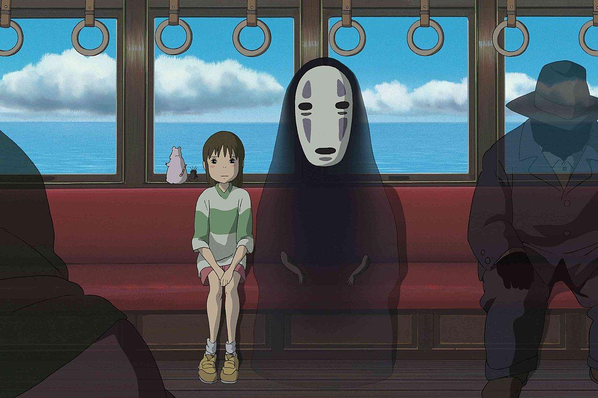 """Imagem do filme de animação """"A Viagem de Chihiro. A visão que temos é a da parte interna de um trem: o banco avermelhado que se estende por todo o vagão e as janelas que revelam o céu azulado do lado de fora. Ao centro, sentados no banco, estão Chihiro, uma garota asiática, de pele branca, bochechas rosadas e cabelos castanhos presos num rabo de cavalo, vestindo uma camiseta branca e verde, um short vermelho e tênis amarelos; e Sem Rosto, uma criatura inteira preta, com uma máscara branca no lugar do rosto, que é ligeiramente transparente, podendo se ver parte do fundo através dele. Eles olham para frente, com o semblante reflexivo. Ao lado deles, pode-se ver sentadas algumas figuras misteriosas, usando ternos e chapéus pretos que cobrem totalmente seus rostos. Elas, assim como Sem Rosto, também são ligeiramente transparentes, podendo se ver parte do fundo através delas. Além deles, vemos, apoiados na janela, um ratinho rosa e um mosquito preto, que observam a paisagem pelo vidro.]"""
