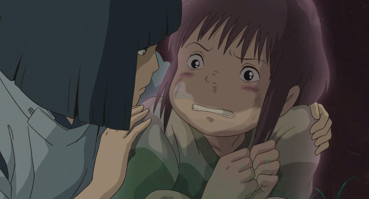 """Imagem do filme de animação """"A Viagem de Chihiro"""". A cena se passa de noite. Vemos Chihiro: uma garota asiática, de pele branca, bochechas rosadas e cabelos castanhos presos em um rabo de cavalo, vestindo uma camisa branca e verde. A menina está ligeiramente transparente, como se estivesse gradualmente sumindo, e é possível ver parte do fundo através dela. Ela está claramente assustada e totalmente retraída, as mãos coladas uma na outra, as pernas dobradas, e o seu olhar é de completo medo. Ao lado dela, tentando consolá-la, com seus braços a envolvendo, está Haku: um homem asiático, de pele clara e cabelos pretos que formam uma franja em sua testa e se alongam até os ombros nas laterais. Ele usa um kimono azul e olha para a garota, seu semblante calmo e preocupado.]"""