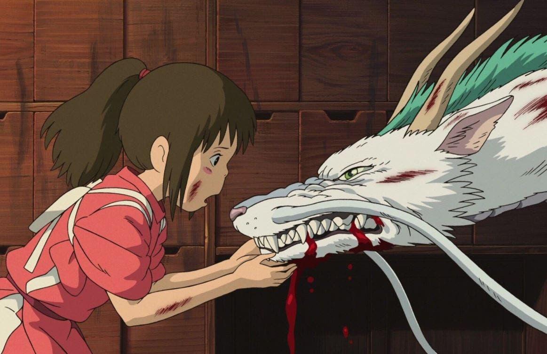 """Imagem do filme de animação """"A Viagem de Chihiro"""". A cena mostra Chihiro: uma garota asiática, de pele branca, bochechas rosadas e cabelos castanhos presos em rabo de cavalo, vestindo um kimono vermelho. Ela aparece de perfil enquanto segura, claramente preocupada, a cabeça de Haku: um dragão asiático branco com crinas verdes e dois chifres na cabeça. Sua boca está sangrando, seu corpo está cheio de machucados, e ele está evidentemente bravo e irritado, mostrando seus dentes afiados.]"""
