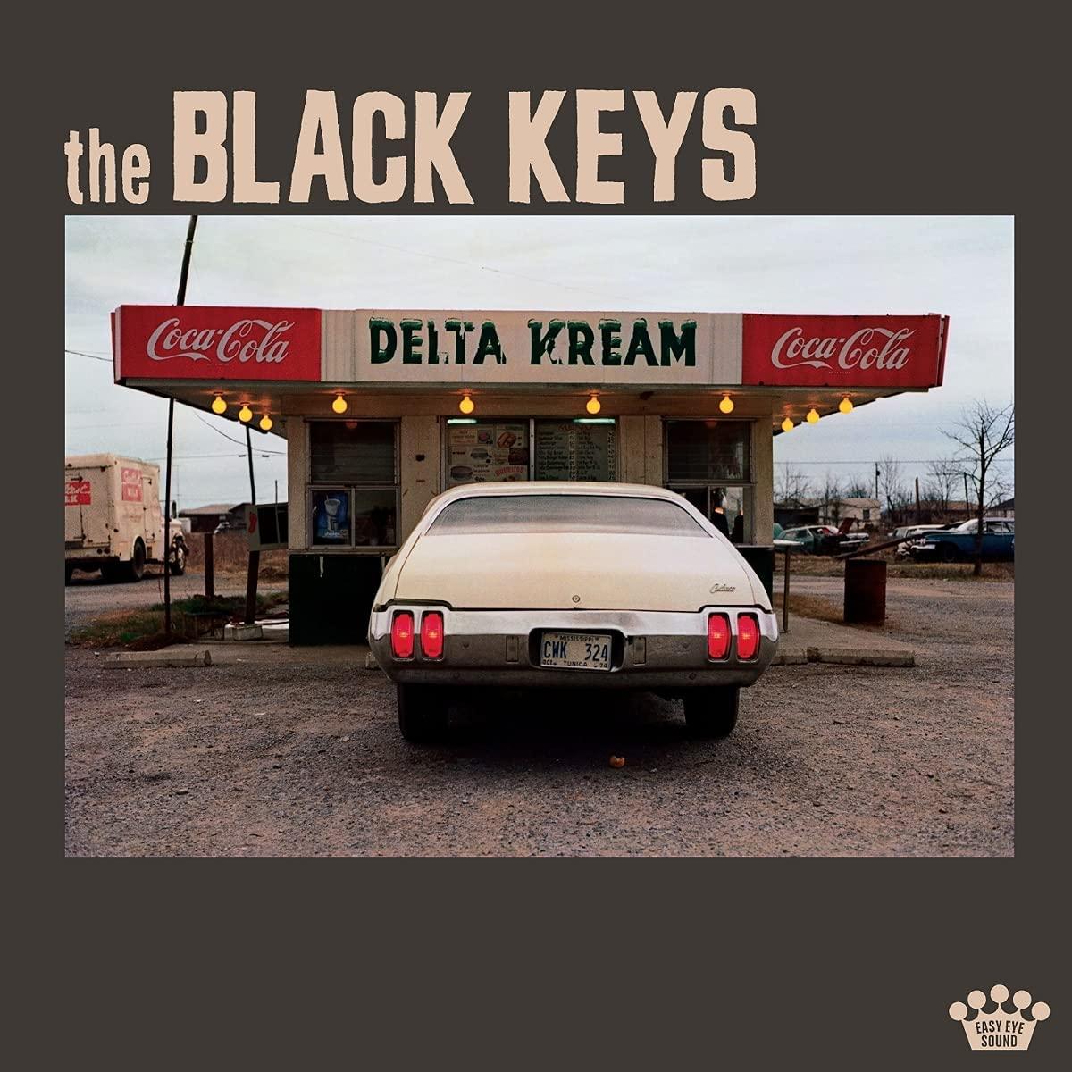 Capa do CD Delta Kream. Apresenta o título da banda The Black Keys acima. Em uma fotografia quadrada, há um carro branco estacionado no centro, em frente a uma loja chamada Delta Kream, que possui dois símbolos da Coca-Cola ao lado do nome. O chão é de terra batida.