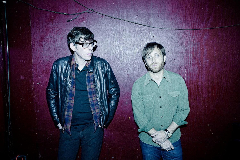 Foto de Patrick Carney e Dan Auerbach. Os dois são homens brancos, e Patrick é mais alto que Dan. Patrick tem cabelo curto e liso de cor preta, está com as duas mãos no bolso da calça, usa um óculos com armação preta, uma jaqueta de couro preta, uma camisa xadrez azul e roxa e uma camiseta preta. Dan é loiro, possui cabelo curto e liso, pouca barba, e está com uma camisa verde. Os dois estão encostados em uma parede cor vinho.