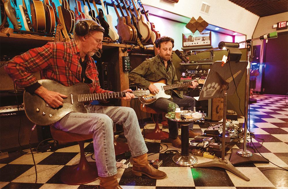 Foto de Kenny Brown e Dan Auerbach. Os dois são homens brancos e estão em um estúdio, com guitarras penduradas ao fundo. Kenny é mais velho que Dan, está com fones de ouvido na cor preta, camisa xadrez vermelha, branca e preta, e toca uma guitarra preta. Está usando uma calça jeans clara e botas na cor marrom. Dan está com fones de ouvido na cor preta, uma camisa verde, tocando uma guitarra branca, laranja e preta, com uma maleta de pedais aberta no chão. Ele usa uma calça jeans escura e botas na cor marrom. Ambos estão sentados em bancos da cor marrom.