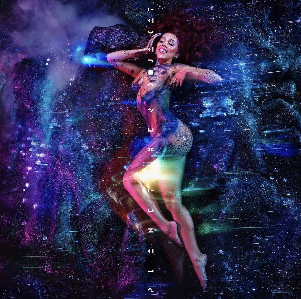 Capa do álbum Planet Her, da cantora Doja Cat. A foto mostra a cantora Doja Cat, uma mulher negra de olhos castanhos e cabelos vermelhos, e ela está deitada de lado. Ao fundo há a representação do espaço sideral.