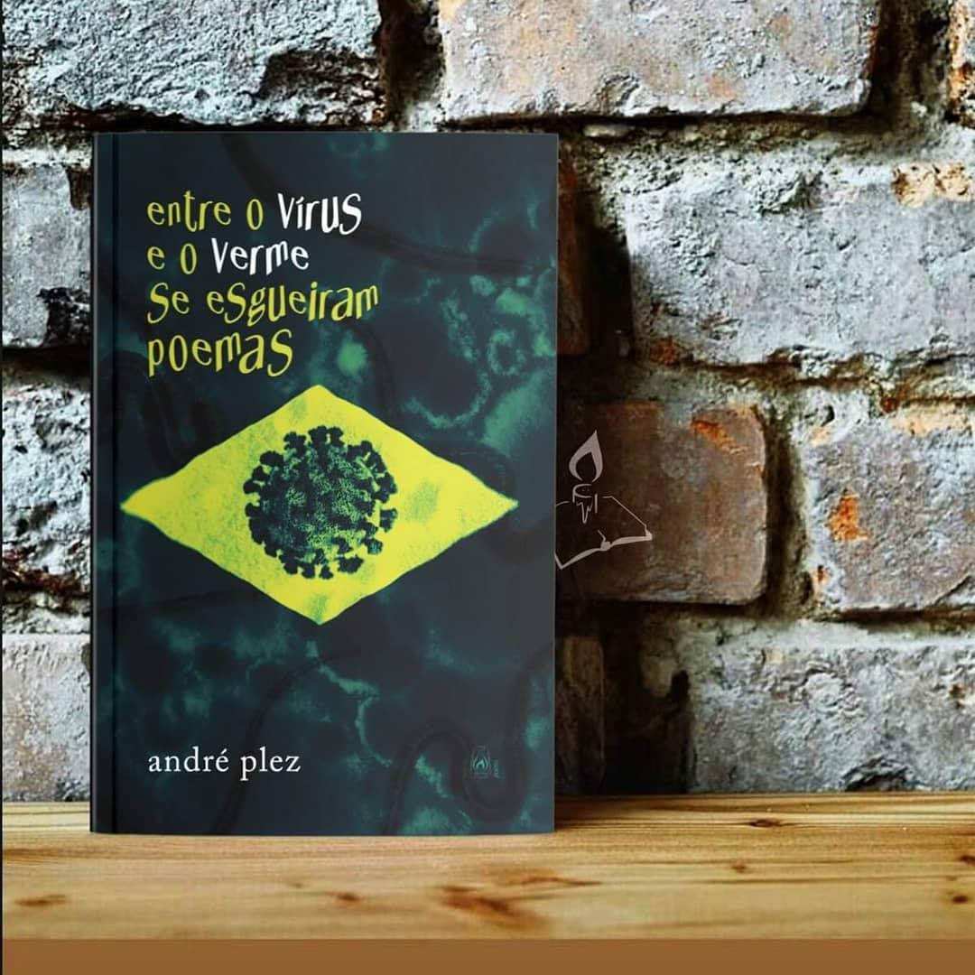 """Capa do livro Entre o vírus e o verme se esgueiram poemas. Fotografia quadrada. Ao fundo, uma parede de tijolos expostos, de cor cinza, apoia o livro. Na parte superior da capa, pode-se ler """"Entre o vírus e o verme se esgueiram poemas"""" em letras tortas, de cor verde claro, com exceção de """"vírus"""" e """"verme"""", grafados em branco. No centro da capa, sobre um fundo verde escuro, há um losango verde claro com a imagem do novo coronavírus, fazendo alusão à bandeira do Brasil. No canto inferior esquerdo da capa, lê-se """"André Plez"""" em letras brancas. Sob o livro, há um apoio de madeira."""