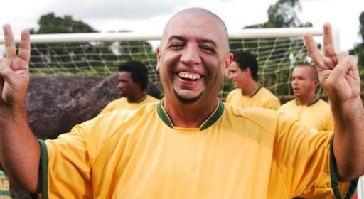 """A imagem mostra Bussunda com a camisa amarela (principal) da Seleção. Bussunda está em um campo de futebol. Ele é um homem branco, gordo, careca, sorridente e faz um gesto de """"paz e amor"""" com as duas mãos. Bussunda preenche quase toda a imagem, porém é possível observar que atrás dele há outros homens com a camisa da Seleção Brasileira."""