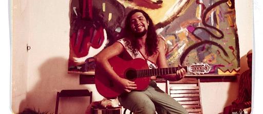 Bussunda no auge de sua juventude, com uns vinte e poucos anos de idade tocando violão na sala de casa. O jovem aparece sorridente, magro, com um cabelo longo, sem camisa, com um violão no colo, sentado em uma cadeira no meio de uma sala de estar. A imagem também retrata um quadro colorido com uma pintura abstrata.