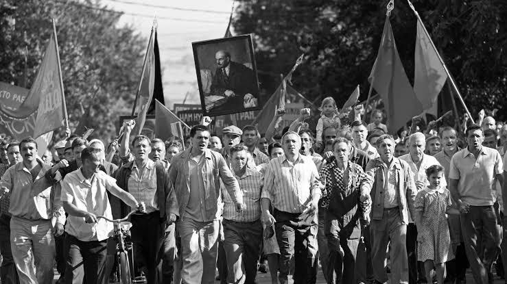 cena do filme Caros Camaradas! em branco e preto na qual os trabalhadores vão às ruas para protestar. A imagem apresenta dezenas de proletários, majoritariamente homens, erguendo bandeiras e um quadro de Lenin.